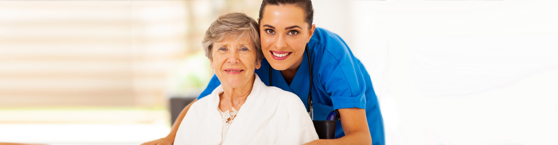 smiling nurse and her old woman patient